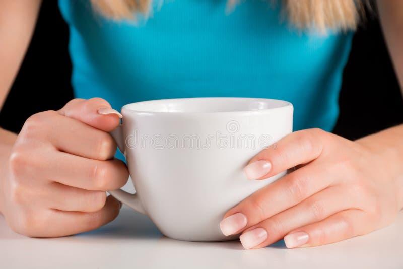 Le mani della donna con Ombre manicure la tenuta la tazza di caffè o del tè immagini stock libere da diritti