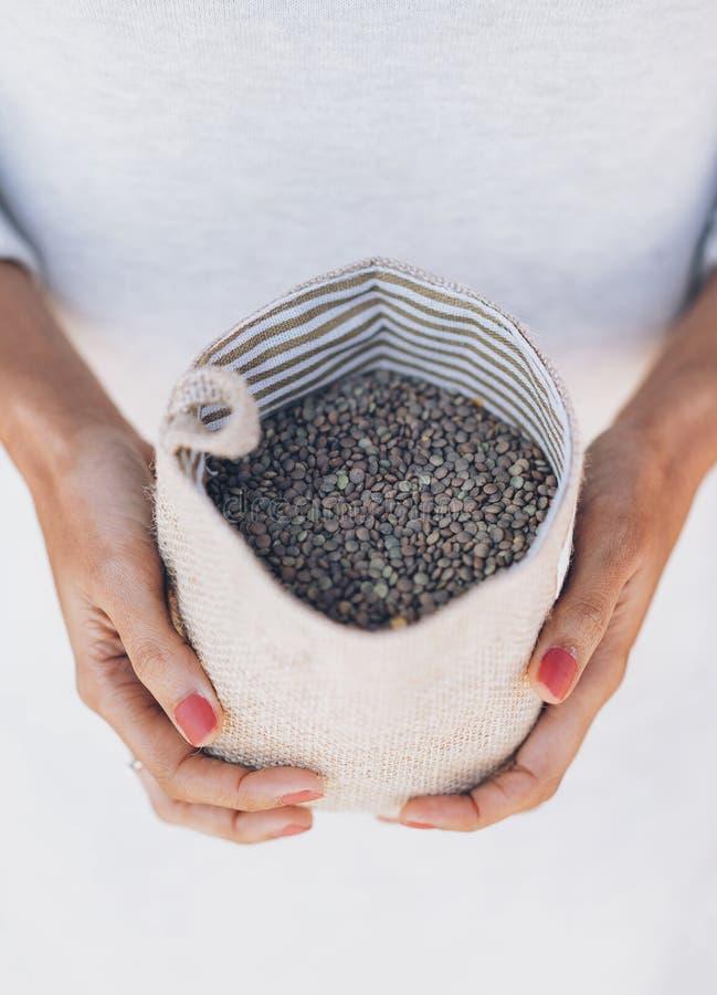 Le mani della donna con una manciata di lenticchie marroni vegetariane fotografia stock libera da diritti
