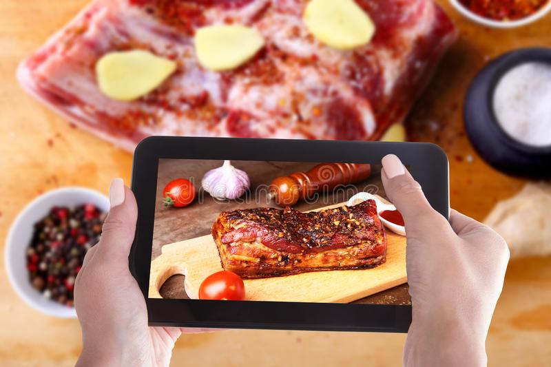Le mani della donna con uno smartphone sullo schermo di cui le costole di carne di maiale arrostite della foto arrostiscono col b fotografia stock libera da diritti