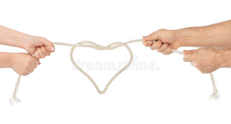 Le mani della donna e dell'uomo con cuore hanno modellato la corda fotografie stock