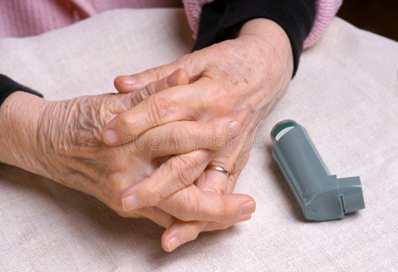 Le mani della donna ed inalatore di asma immagine stock