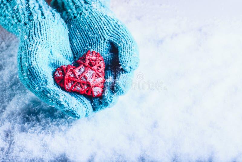 Le mani della donna in guanti tricottati alzavola leggera stanno tenendo il bello cuore rosso d'annata intrecciato in una neve Co immagini stock libere da diritti