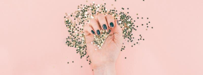 Le mani della donna hanno coperto i coriandoli dorati delle stelle sul rosa fotografie stock libere da diritti