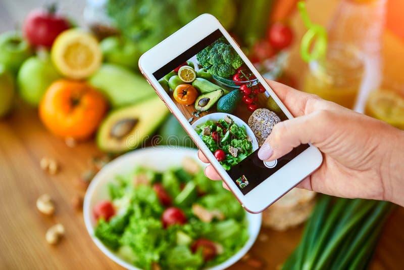 Le mani della donna prendono la foto dell'alimento dello smartphone dell'insalata delle verdure con i pomodori ed i frutti Fotogr immagine stock libera da diritti