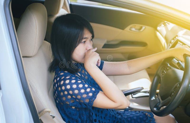 Le mani della donna schiacciano e toccando il suo naso con di cattivo odore in un'automobile fotografia stock