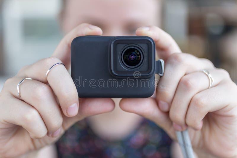 Le mani della donna si chiudono sulla tenuta della macchina fotografica nera piccola di azione che prende un video o una foto immagini stock libere da diritti