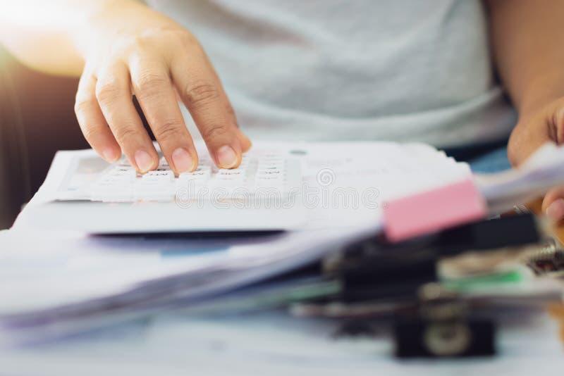 Le mani della donna sta calcolando i documenti di spese a casa fotografia stock libera da diritti