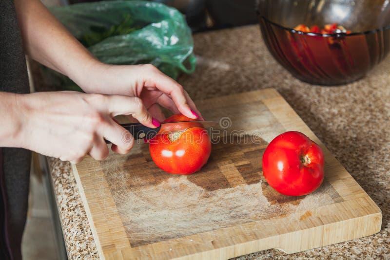 Le mani della donna stanno tagliando il pomodoro rosso fotografia stock libera da diritti