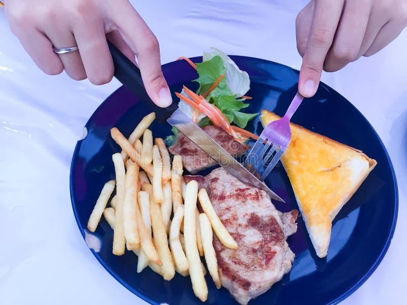Le mani della donna stanno tenendo una forcella e un coltello per tagliare la bistecca Ciò è bistecca grigliata di braciola di ma fotografia stock libera da diritti
