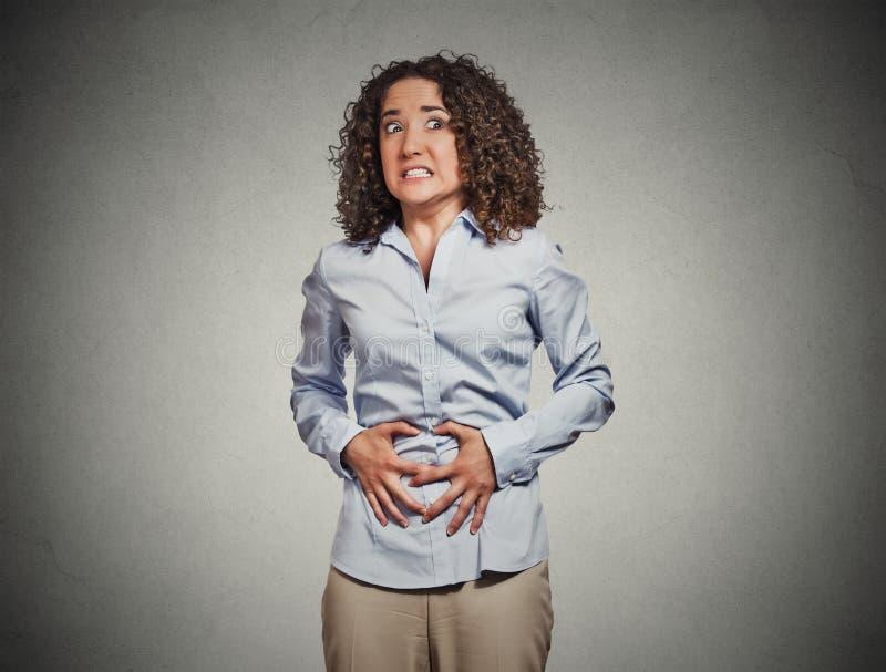 Le mani della donna sullo stomaco che ha cattivi dolori fanno soffrire immagini stock libere da diritti