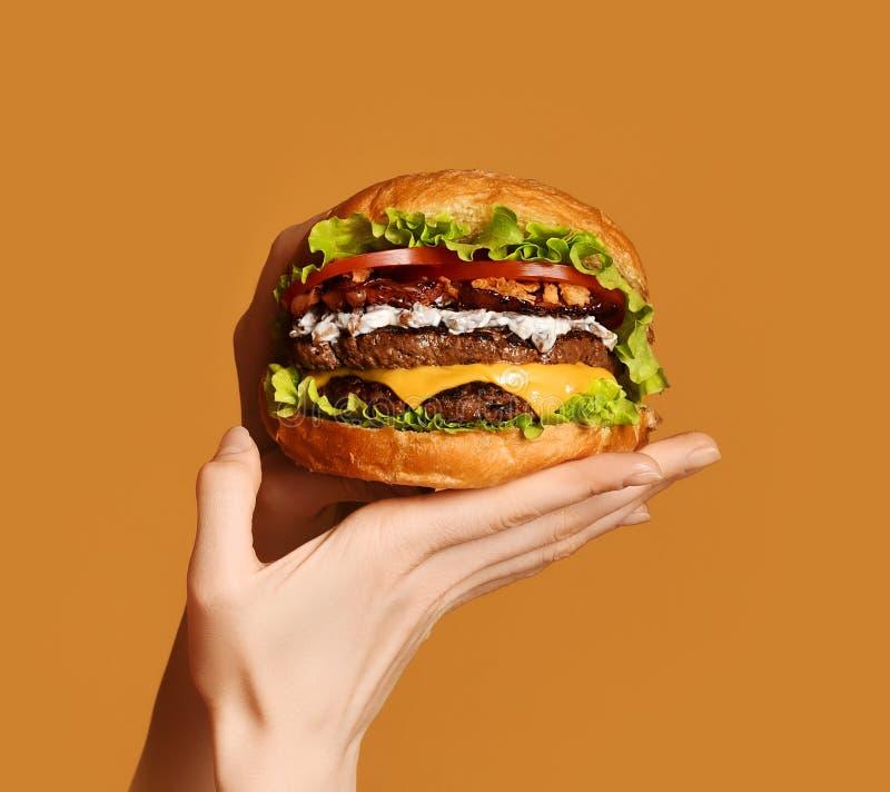 Le mani della donna tengono il grande doppio panino dell'hamburger del cheeseburger con il manzo ed il bacon su giallo fotografie stock libere da diritti