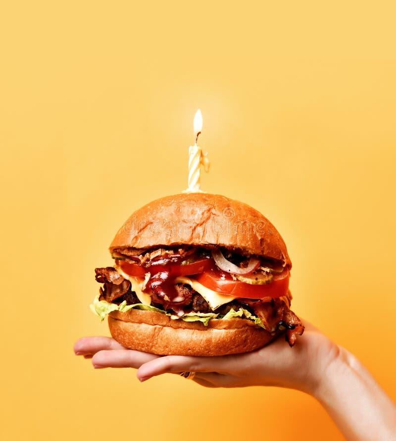 Le mani della donna tengono il grande panino saporito del barbecue dell'hamburger con il manzo di marmo e la candela accesa per l fotografia stock libera da diritti