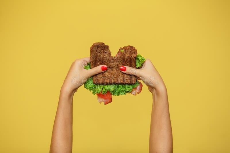 Le mani della donna tengono il panino pungente su fondo giallo Concetto di promozione del panino immagini stock