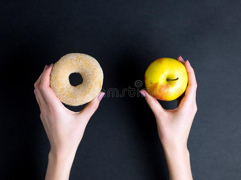 Le mani della donna tengono la ciambella e la mela dolci dello zucchero su fondo scuro, la vista superiore, posto per testo fotografie stock libere da diritti