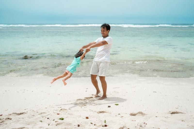 Le mani della figlia della tenuta del padre quando gioca l'oscillazione gira sulla spiaggia fotografia stock libera da diritti