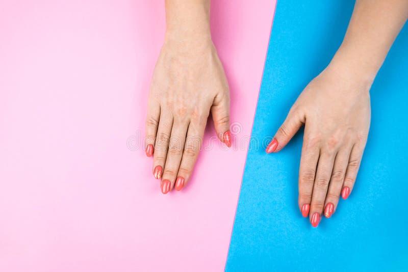 Le mani della giovane donna adorabile su fondo colorato immagini stock libere da diritti
