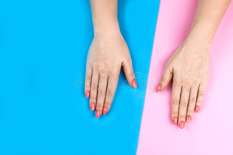 Le mani della giovane donna adorabile su fondo colorato immagini stock