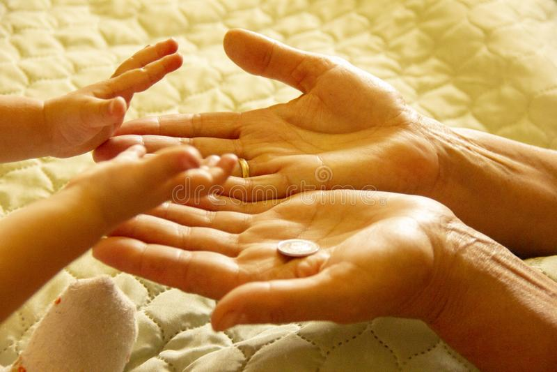 le mani della nonna s sono palme su le mani del bambino che ordinano soldi nelle mani della nonna fotografie stock libere da diritti