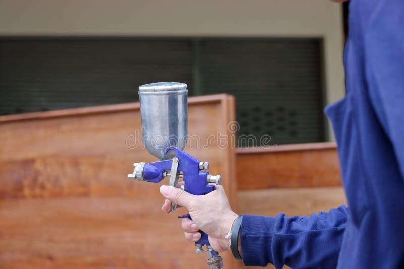 Le mani della pittura di spruzzo della tenuta del lavoratore dell'industria sparano nella fabbrica immagini stock