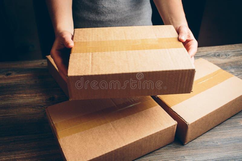 Le mani della ragazza che tengono il pacchetto sulla tavola fotografia stock libera da diritti