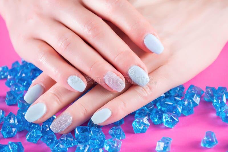 Le mani della ragazza con il manicure blu sul dito inchioda la mano della tenuta sui molti cristallo o pietra preziosa blu fotografia stock