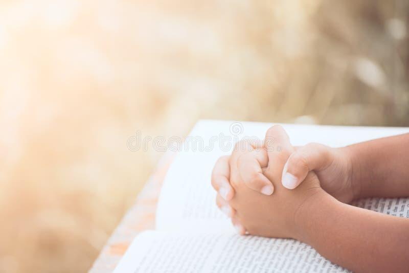 Le mani della ragazza del piccolo bambino hanno piegato nella preghiera su una bibbia santa fotografia stock