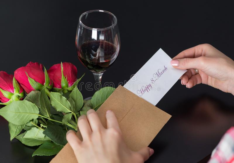Le mani della ragazza prende ad un messaggio 8 felici Marzo su carta dalla retro busta sullo scrittorio nero con il mazzo della r fotografia stock libera da diritti