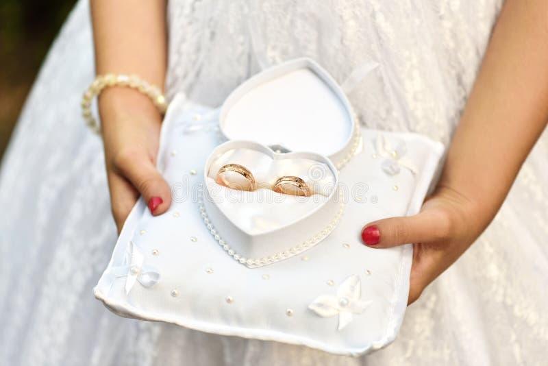 Le mani della ragazza tengono le fedi nuziali in una scatola in forma di cuore fotografia stock