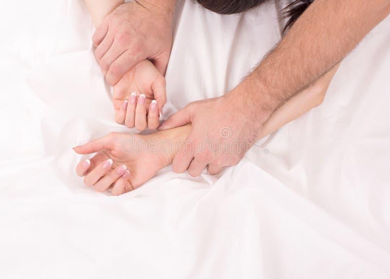 Le mani delle coppie che fanno sesso su bianco hanno sgualcito lo strato, fuoco sulle mani fotografia stock