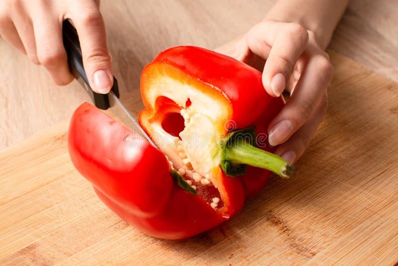 Le mani delle donne che cuting un peperone dolce a metà sul tagliere immagini stock libere da diritti