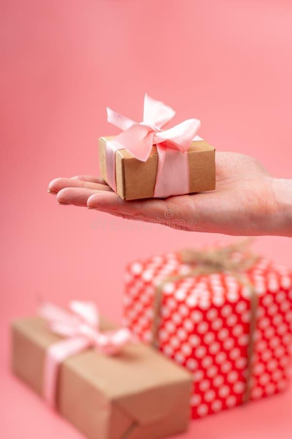 Le mani delle donne che giudicano il contenitore di regalo imballato in carta kraft su fondo rosa Carta di festa per il giorno de immagini stock