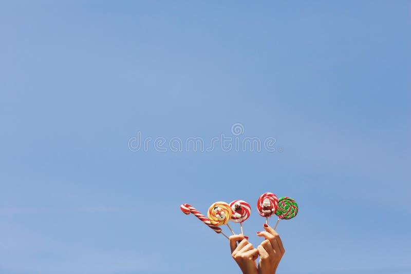 Le mani delle donne che tengono le caramelle colorate di Natale sui precedenti del cielo blu Spazio per testo Concetto di Natale immagini stock