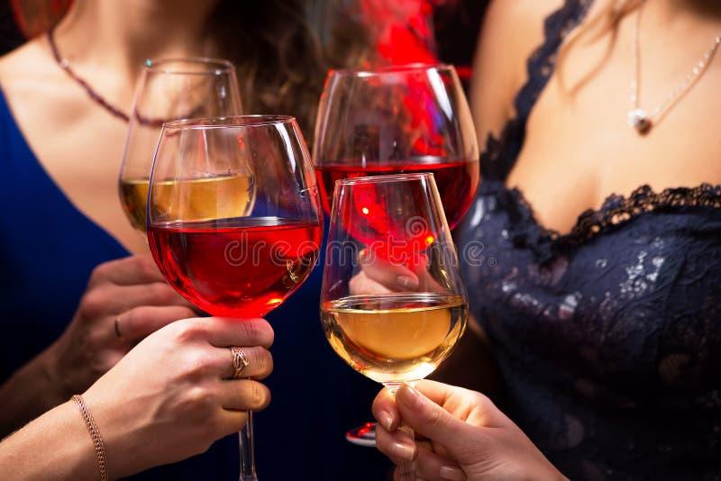 Le mani delle donne con i bicchieri di vino a cristallo fotografia stock libera da diritti