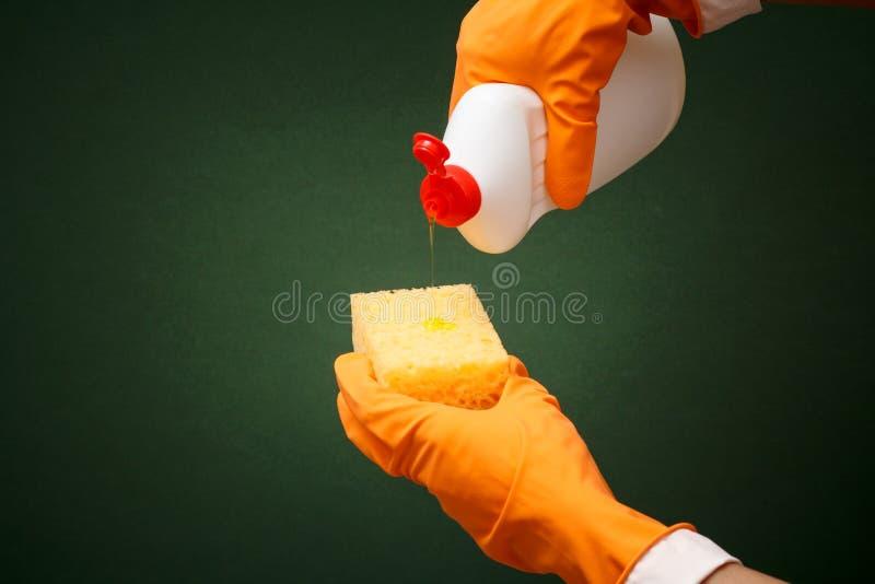 Le mani delle donne in guanto protettivo con la bottiglia del liquido di lavatura dei piatti immagine stock