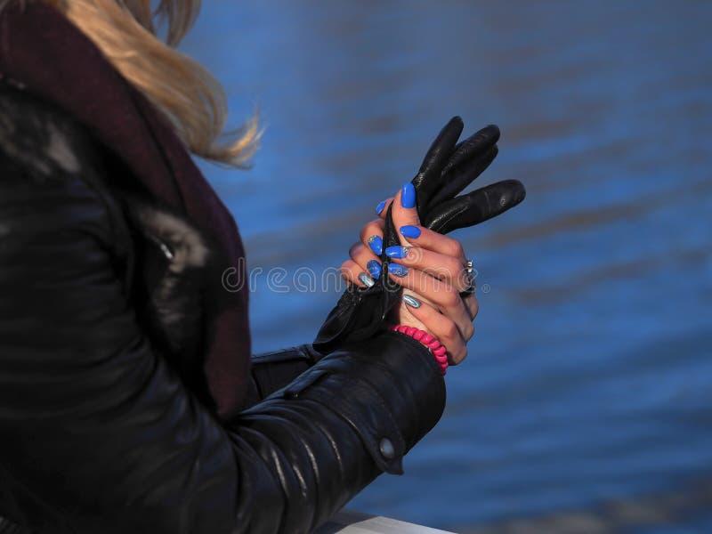 Le mani delle donne hanno piegato al polso contro l'acqua immagini stock