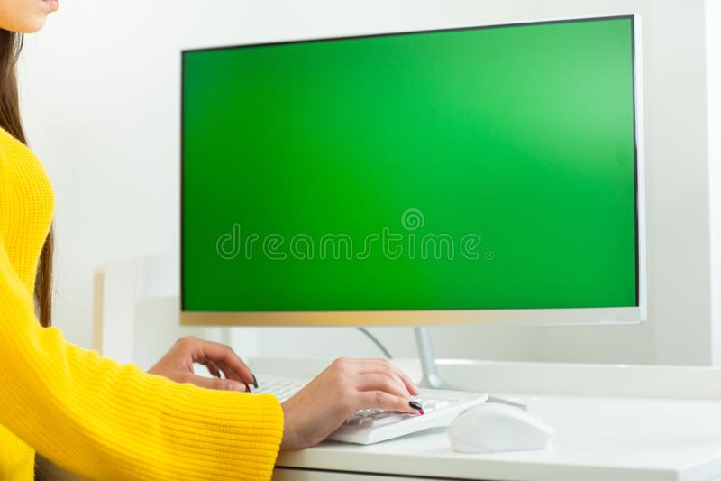 Le mani delle donne si chiudono su, lavorando al computer con lo schermo verde, in un ambiente dell'ufficio fotografie stock libere da diritti