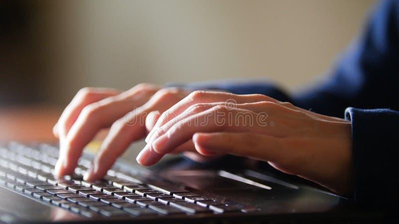 Le mani delle donne stanno stampando sulla tastiera del computer portatile Colpo del dettaglio fotografia stock libera da diritti