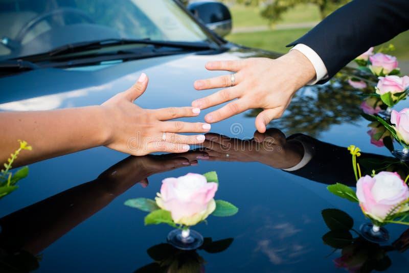 Le mani delle persone appena sposate con gli anelli si chiudono su Arco della stella blu con il nastro blu (involucro di regalo)  fotografie stock