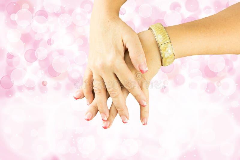 Le mani di bianco di rosa della donna manicured sui chiodi Backround rosa luminoso della sfuocatura del bokeh fotografia stock