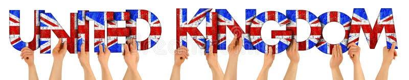 Le mani di braccia della gente che ostacolano l'iscrizione di legno della lettera che forma le parole Regno Unito in bandiera naz fotografie stock