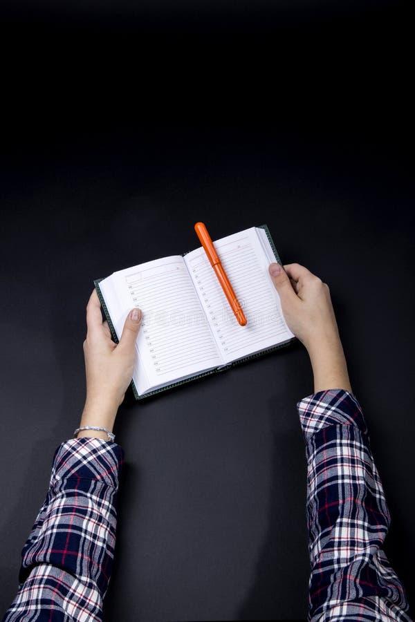 Le mani di un adolescente tengono un taccuino con una penna fotografia stock libera da diritti