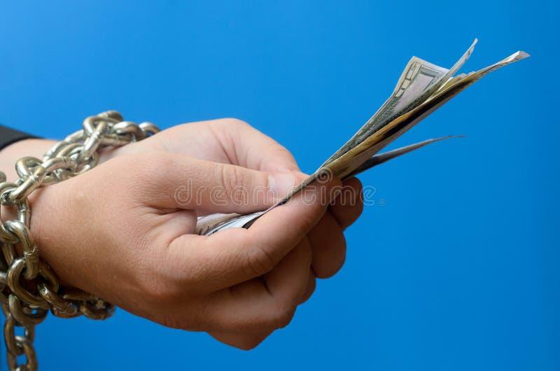Le mani di un limite dell'uomo dai soldi della tenuta e della catena Schiavitù di credito fotografia stock libera da diritti