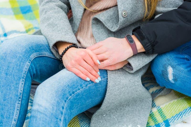 Le mani di un tipo e di una ragazza Una coppia amorosa sta sedendo su un generale e sta tenendo per mano nell'inverno immagine stock libera da diritti