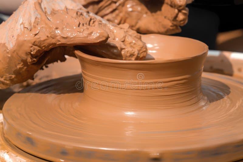 Le mani di un vasaio della via fanno un vaso di argilla su un tornio da vasaio fotografie stock libere da diritti