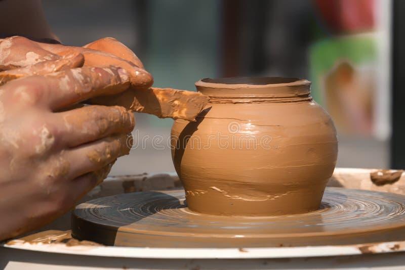Le mani di un vasaio della via fanno un vaso di argilla su un tornio da vasaio immagini stock