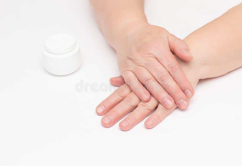 Le mani di una donna anziana su un fondo bianco e di una crema complessa con la vitamina contro le grinze e la tenuta sopra fotografia stock libera da diritti