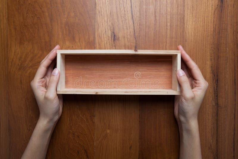 Le mani di una donna due tengono una scatola di legno aperta vuota immagine stock libera da diritti