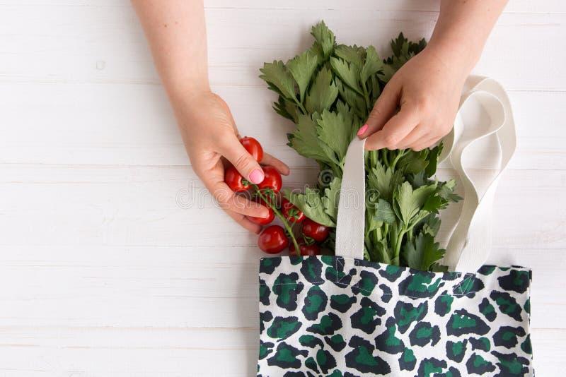 Le mani di una donna eliminano i pomodori organici freschi dal sacchetto della spesa di Eco con la stampa d'avanguardia del model fotografie stock