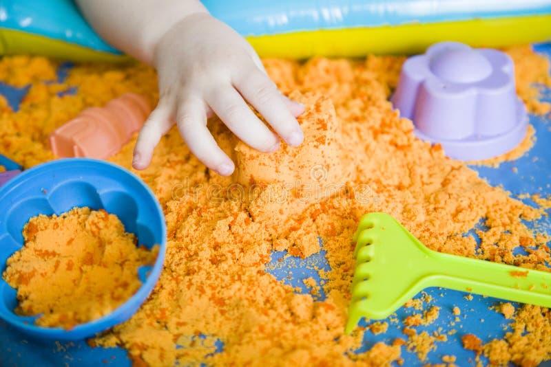 Le mani di una ragazza del bambino che gioca con la sabbia cinetica E immagini stock libere da diritti