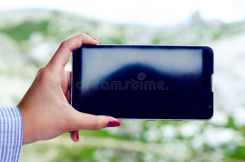 Le mani di Womanche prendono una foto con lo smartphone Sfondo naturale Vista su un telefono cellulare Schermo nero tecnologia fotografia stock libera da diritti